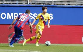 Imagen de un futbolista del Futbol Club Barcelona y otro del Levante C.F. jugando un partido, en el que el futbolista del Barcelona realiza un valgo excesivo de la rodilla, que puede generar la lesión del ligamento lateral interno.