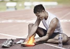 Se observa un deportista sentado en el suelo tocándose el tobillo derecho porque le duele.